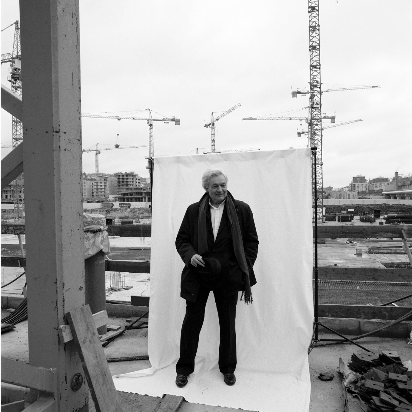 Portrait of a man with a black coat on a construction site