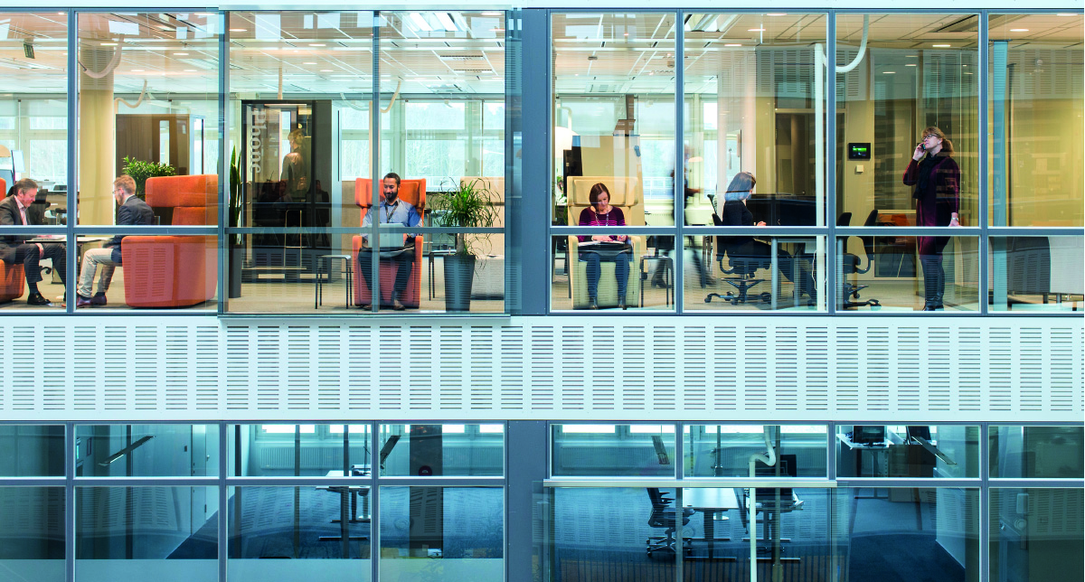 people working in an office in front of a glass facade