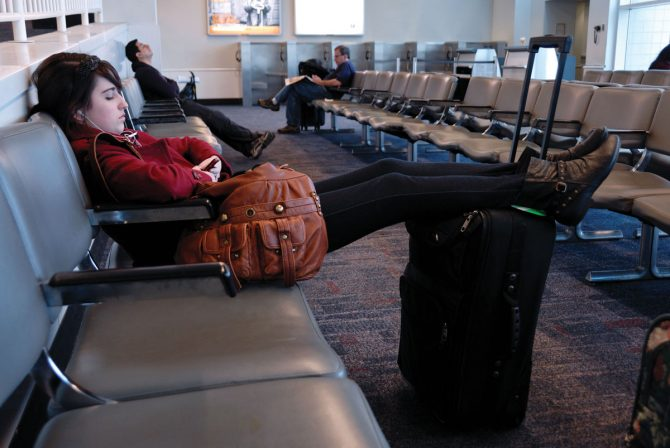 girl with feet on luggage waiting at a gate