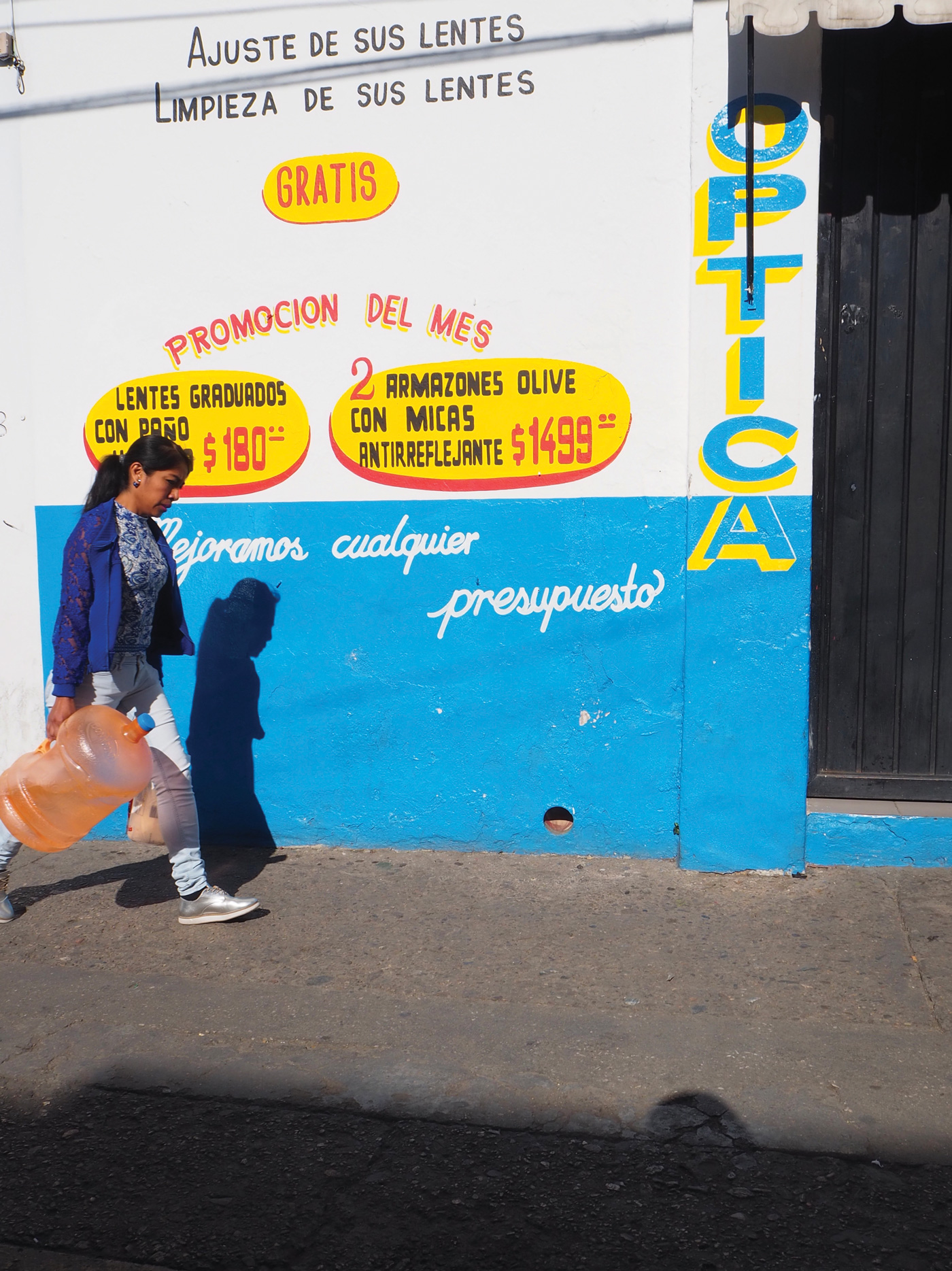 Picture of women walking in front of an advertisement on a wall in Oaxaca, Mexico
