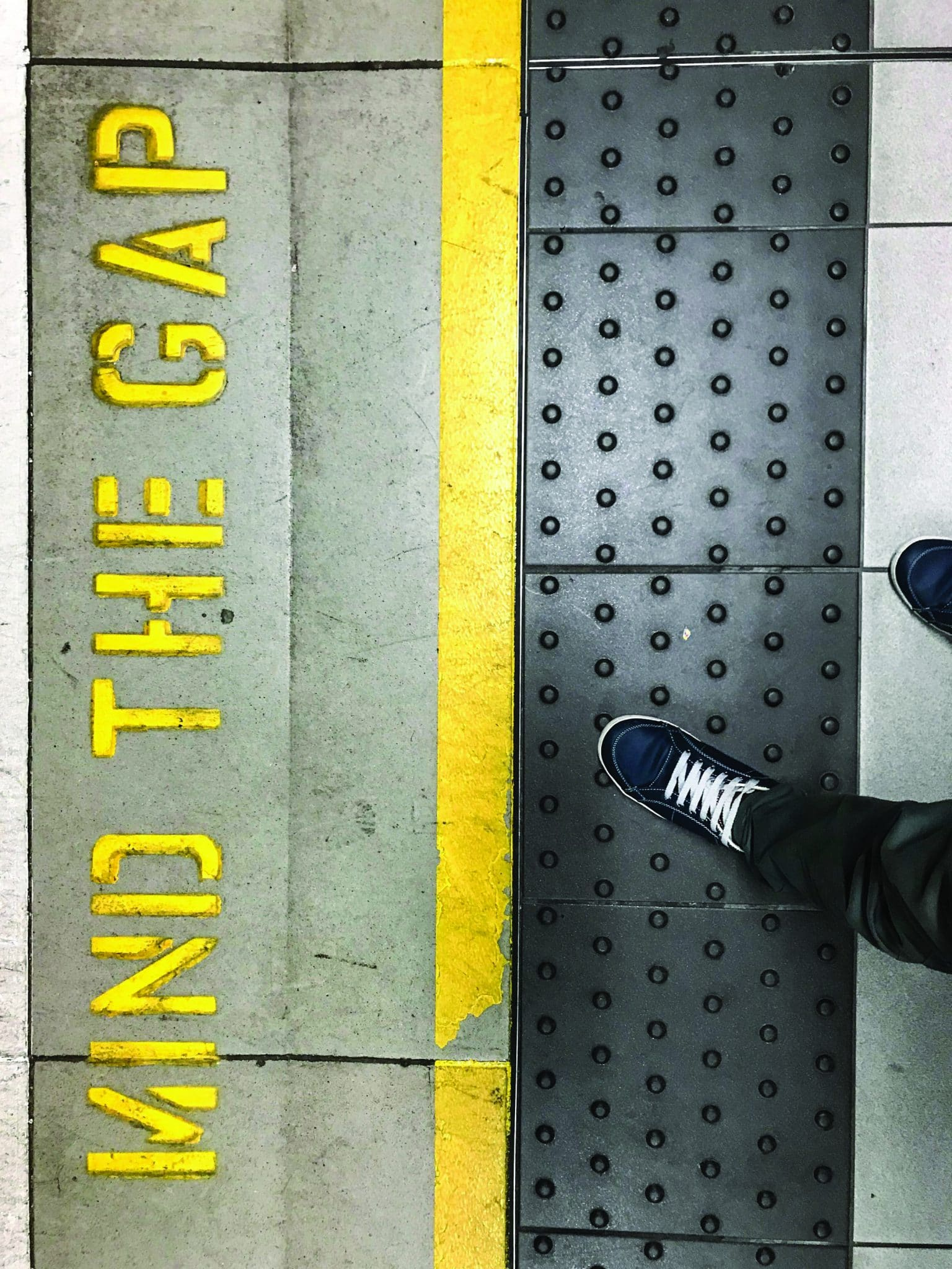 Feet stepping on ruber surface behind yellow safety line of London Underground. Mind the gap sign written on the ground